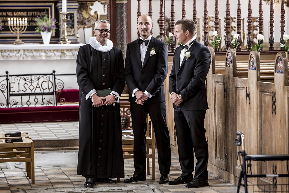 Den forventningsfulde gom flankeret af præsten og forloveren